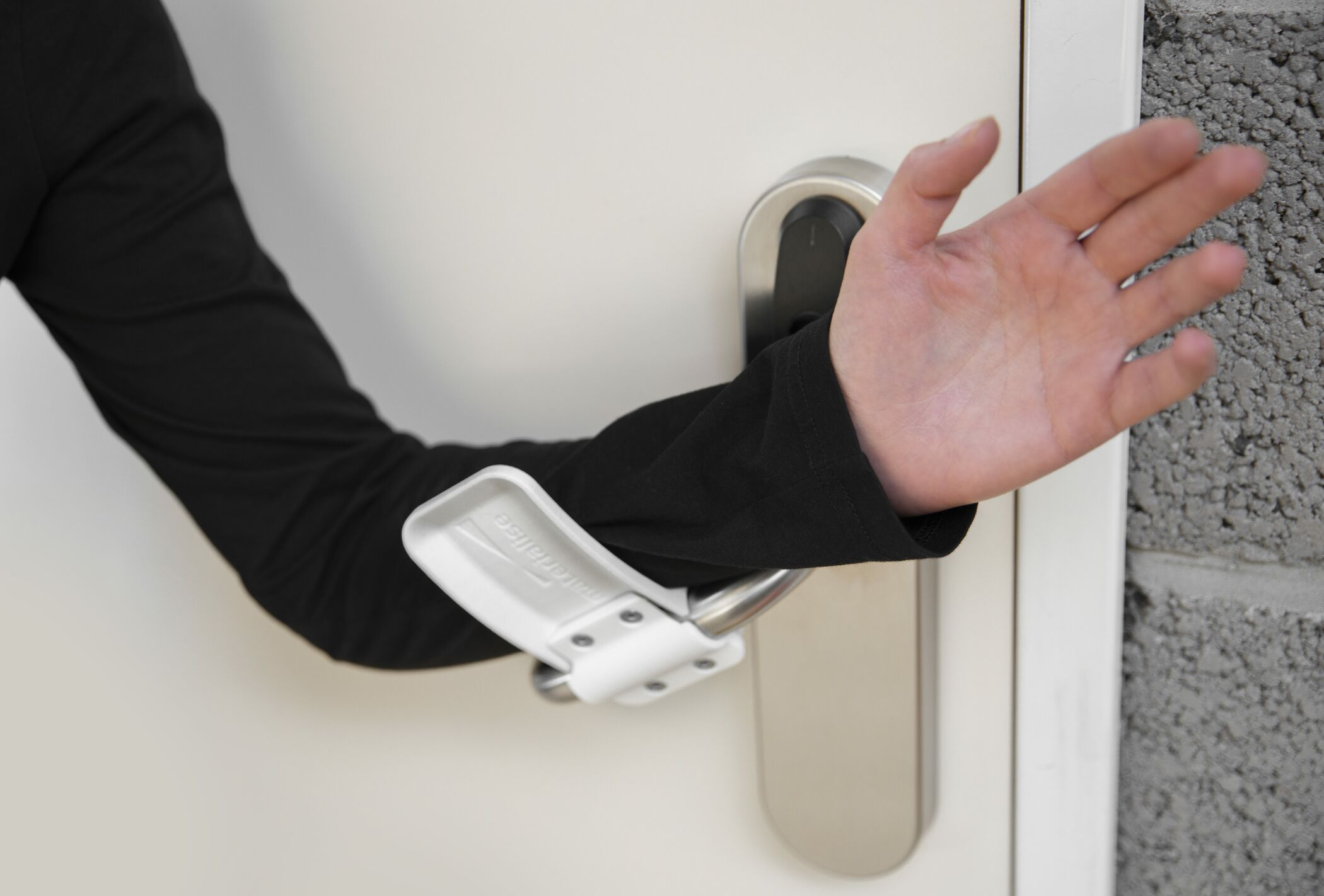 A person demonstrating how to use a hands-free door opener