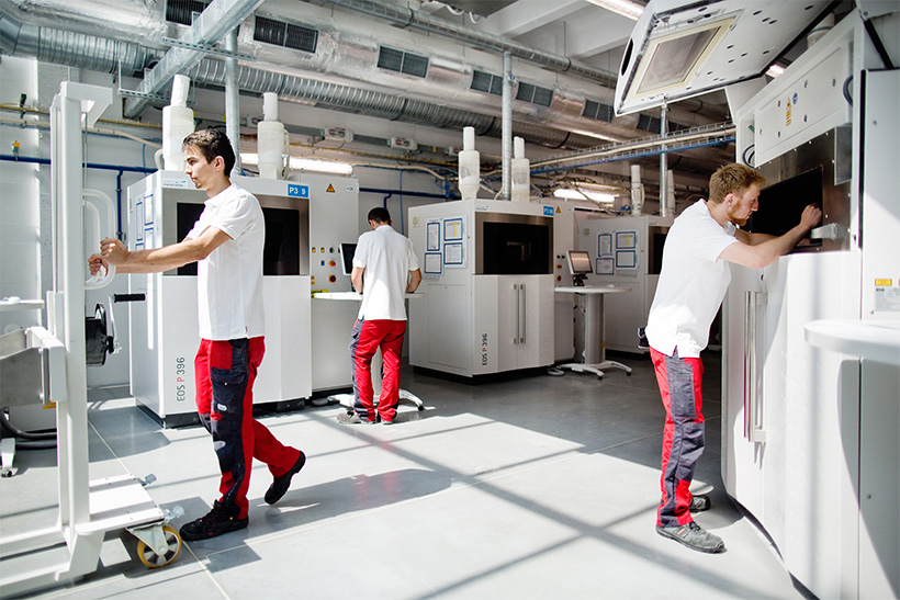 Three production operators work on 3D printing machines in a Selective Laser Sintering facility